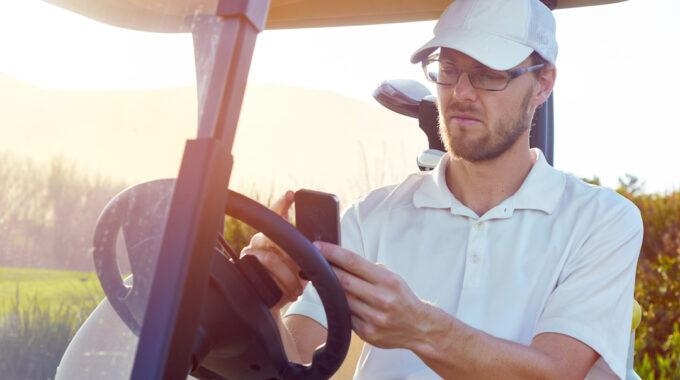 Golfer Using Cellphone App On Cart